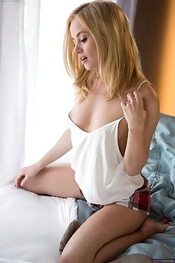 This drool-worthy blonde honey rolls around on her bed while she gets out of her clothes
