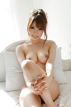 This horny japanese doll rolls around on her big bed and slowly sheds her clothes