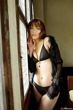 This Japanese hot babe rolls around on a bed in her sexy black lingerie set for the camera