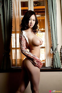 This horny Asian doll strips naked showing off her big natural tits