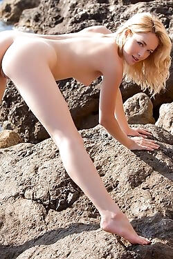The delightful babe is all smiles while she models completely nude on a rocky beach