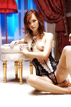 This sizzling redhead strips down to her lace stockings for the camera