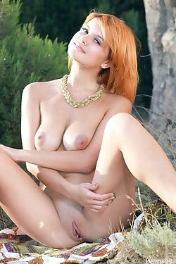 Sassy redhead, models completely naked outdoors today
