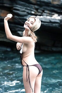She is modeling on a rocky beach while she strips out of her swimsuit