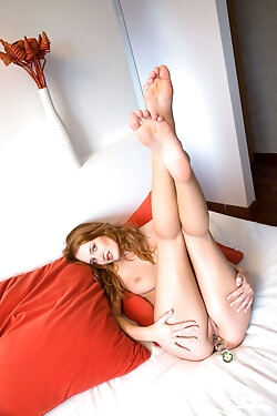 This delectable green-eyed redhead strips and toy fucks her slippery pussy