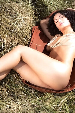 She lies down on some fresh hay and strips out of her clothes for the camera today