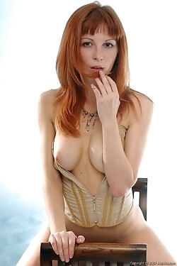 Stripping down to her golden corset, this redhead flaunts her sinful curves