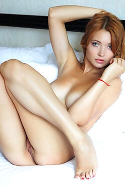 This mouthwatering redhead strips out of her tank top and bares it all for the camera