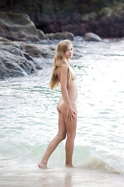She is on the beach, getting a soak in the ocean completely nude