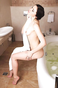 She enjoys her bath, getting her naked body all wet and soapy