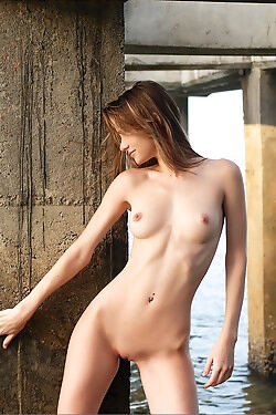 She is modeling nude under a pier while she displays her slender and nubile figure
