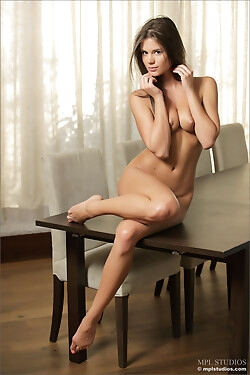 The lovely babe is sitting on a table while she strips naked today