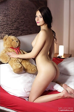 She models with her Teddy bear on a bed while she strips naked