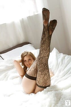 Looking cute in braided pigtails and black stockings, she strikes arousing poses