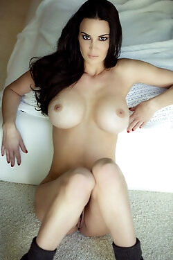 The naughty brunette rolls around on her bed while she bares her sexy curves