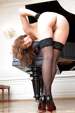 She i models by a piano, stripping down to her sexy black stockings and high heels
