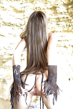 This young girl models in a cave in a scanty leather outfit before stripping and masturbating