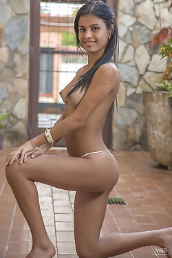 This Latina gorgeous smiles alluringly while she strips down to her white thong