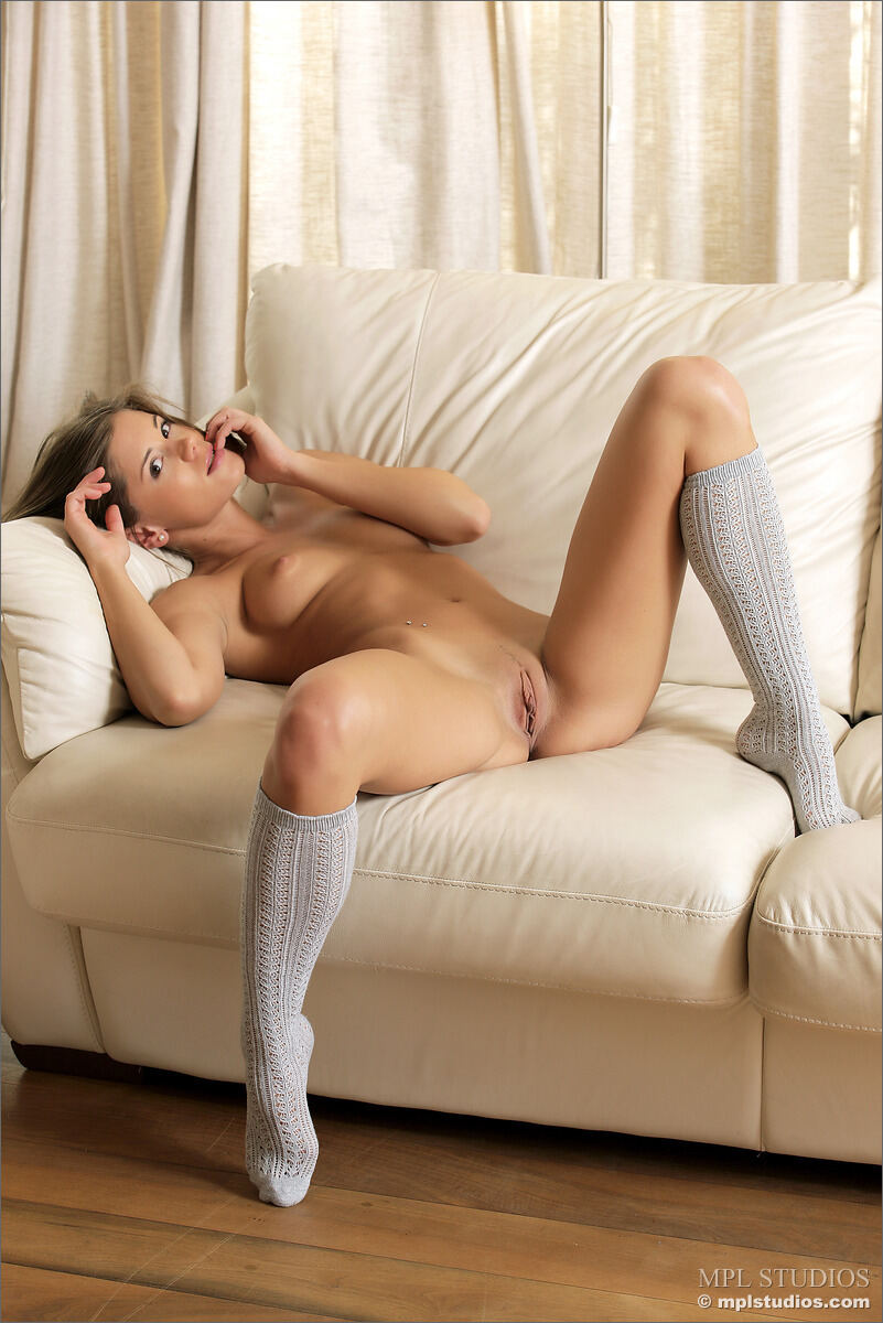 Erotic photos with Caprice: In high socks on a sofa